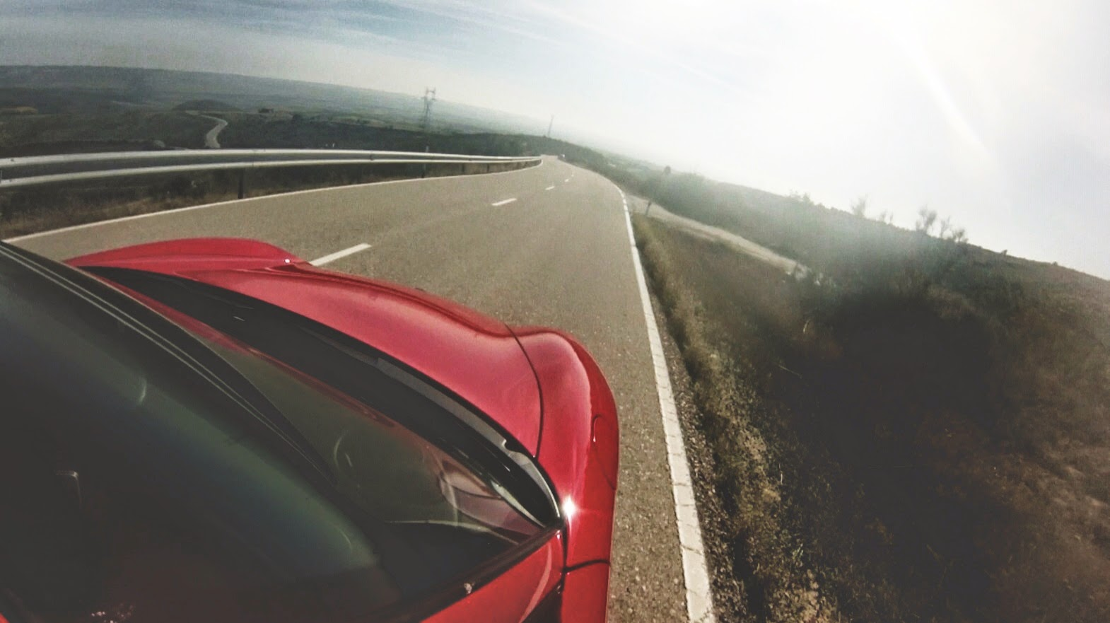 Rotes Fahrzeug fährt auf nebliger Straße