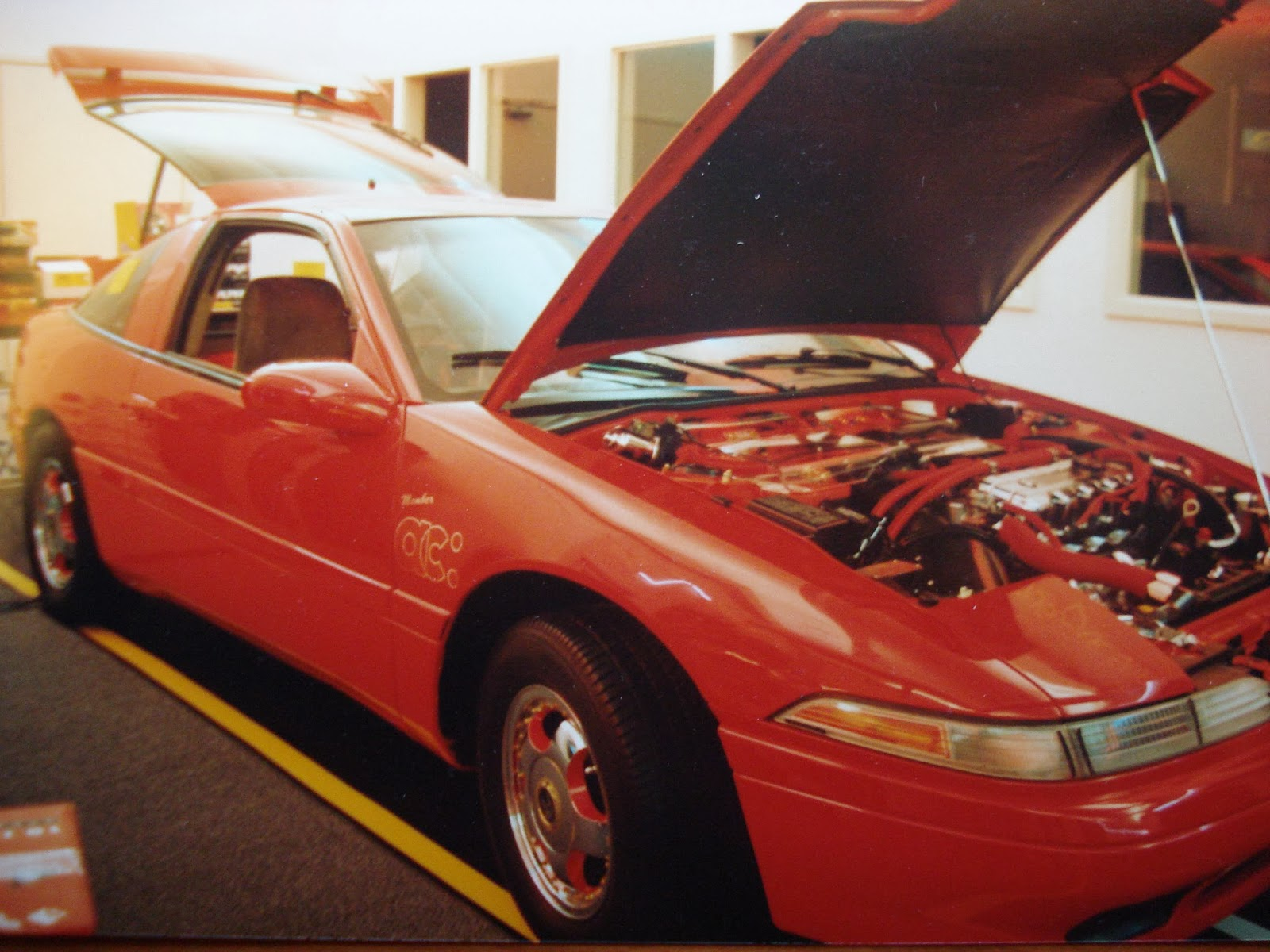 Photo image of the outside of the car (with the engine compartment opened) of Chuck Barbosa's Red Laser as it stood during the winter storage at the end of 1995 and beginning of 1996.