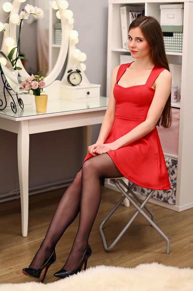 Czerwona sukienka, czarne rajstopy i szpilki