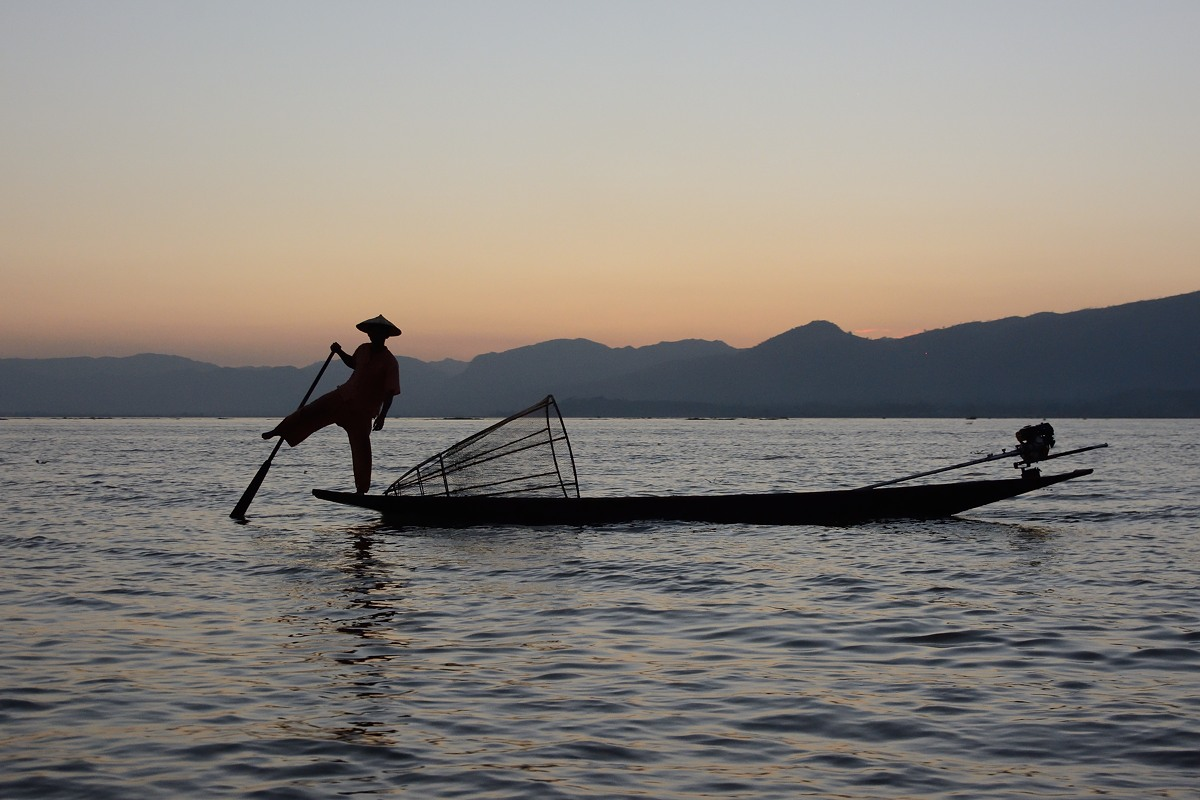 A fisherman using the leg rowing technique on Inle Lake in Myanmar