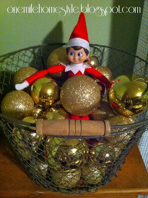 Elf on the Shelf in a basket of ornaments