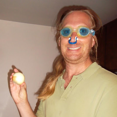 Jonathan Donihue holds onion while wearing goggles and nose plugs