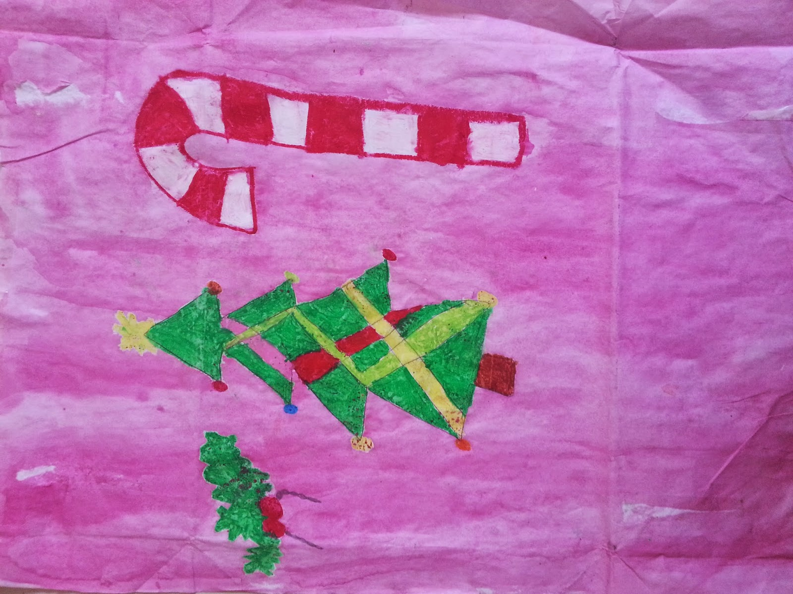 Handmade christmas wrapping paper featuring a tree, holly and candy cane on a pink background