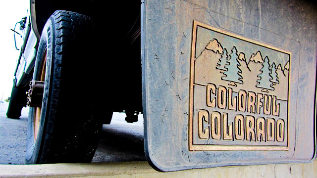Faded and well worn Colorful Colorado mud flaps on a pickup truck in Golden, Colorado.
