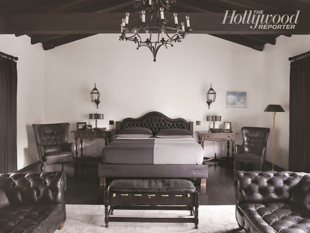 master bedroom with a tufted headboard, ottoman, dueling sofas, two arm chairs, a chandelier and exposed beams