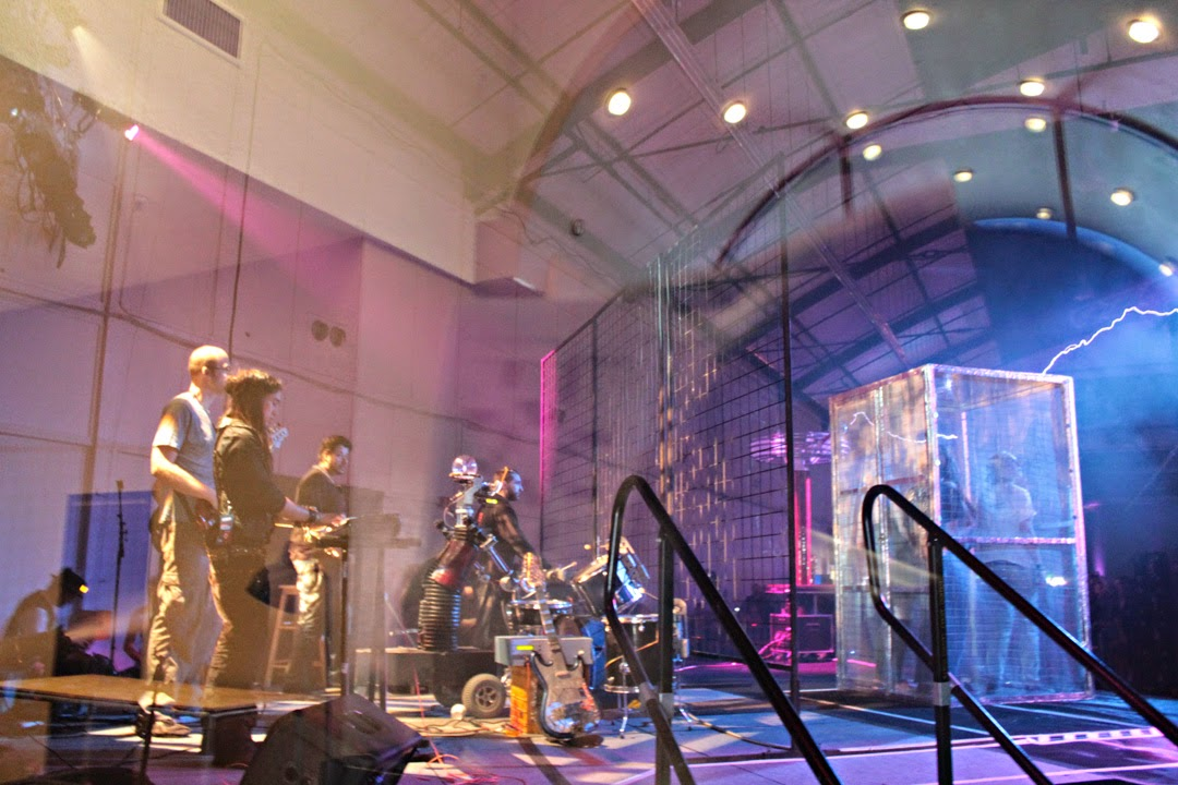 A band triggers Tesla lightning bolts with their music as caged attendees get close to the electricity