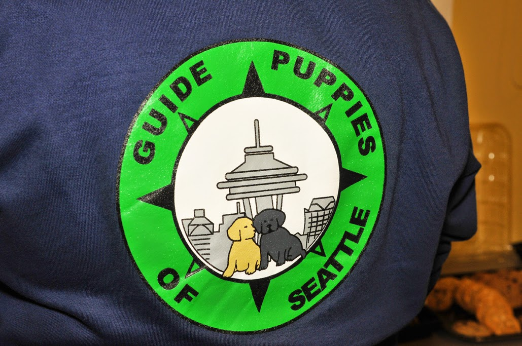 "Image of the back of the blue and green shirt ""Guide Puppies of Seattle"" with the Space Needle and cartoon puppies."