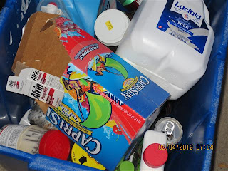 dirty containers and loose paper in blue recycling bin