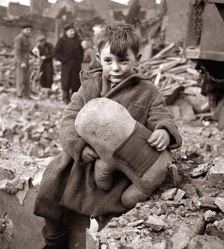 Abandoned boy holding a stuffed toy animal amid ruins following German aerial bombing of London