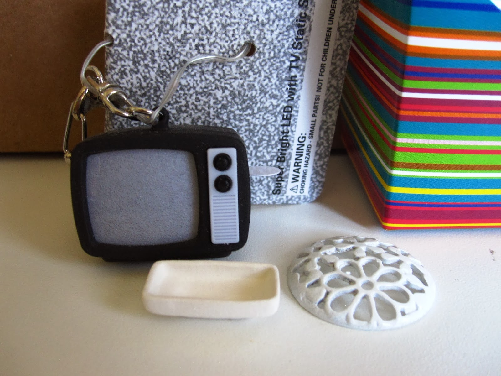 Miniature retro TV, daisy finding and plate