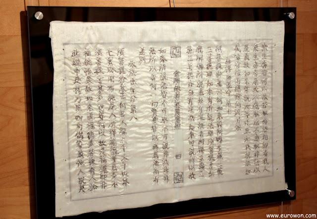 Bordado plateado de escrituras budistas en caracteres chinos