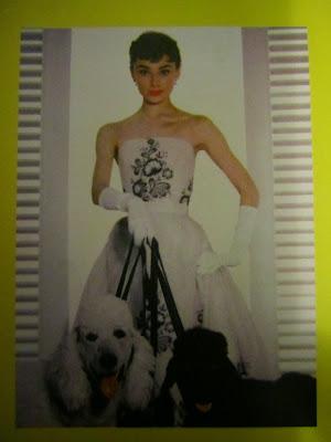 Audrey Herpburn con dos caniches gigantes, uno negro y otro blanco