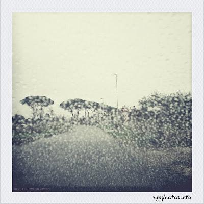 Fotografia di una strada di campagna vista da dietro il parabrezza in una giornata di pioggia