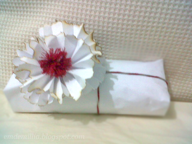 Gift with white paper wrapper and a pom-pom.