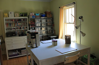 Craft room with new tables, cabinet with hutch and shelves with bins of stamps.