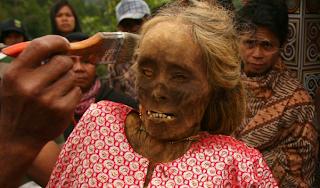 Seorang anggota keluarga membersihkan mumi sebelum memberikan pakaian baru dalam ritual di Kabupaten Toraja Provinsi Sulawesi Selatan di Indonesia