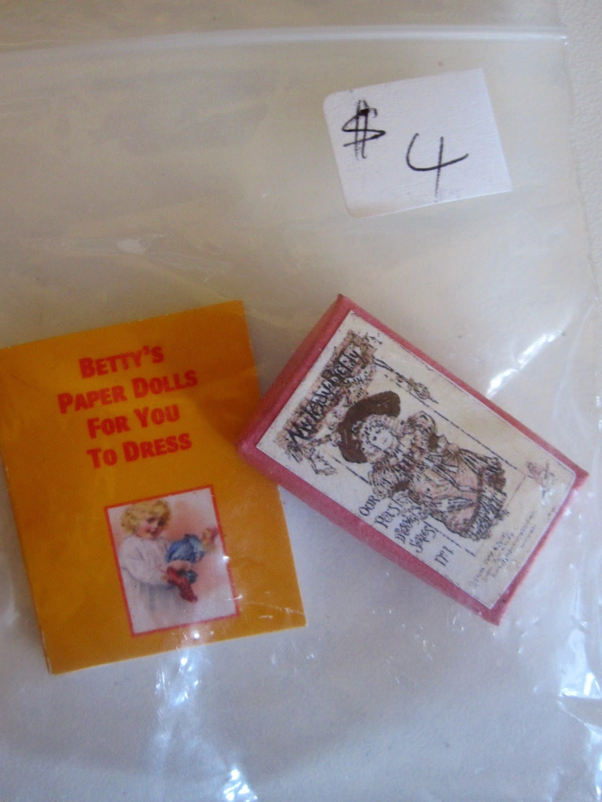 Miniature book of paper dolls and box with image of a Victorian doll on the front, in a bag priced at $4.