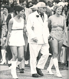 Colonel Sanders walking with 2 young women