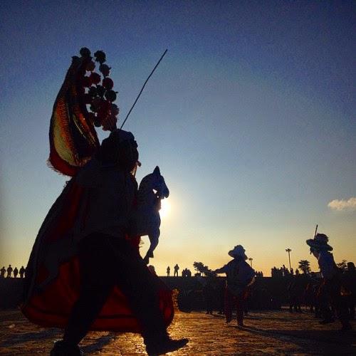 Unos danzantes aparecen bailando la danza  de los Santiagos. En esta danza, un hombre  disfrazado del Apostol Santiago, montado  en un caballo blanco, persigue a los diablos  hasta que los derrota.