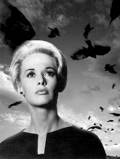 Vintage photo of Tippi Hedren with blonde hair and a black dress in front of birds.