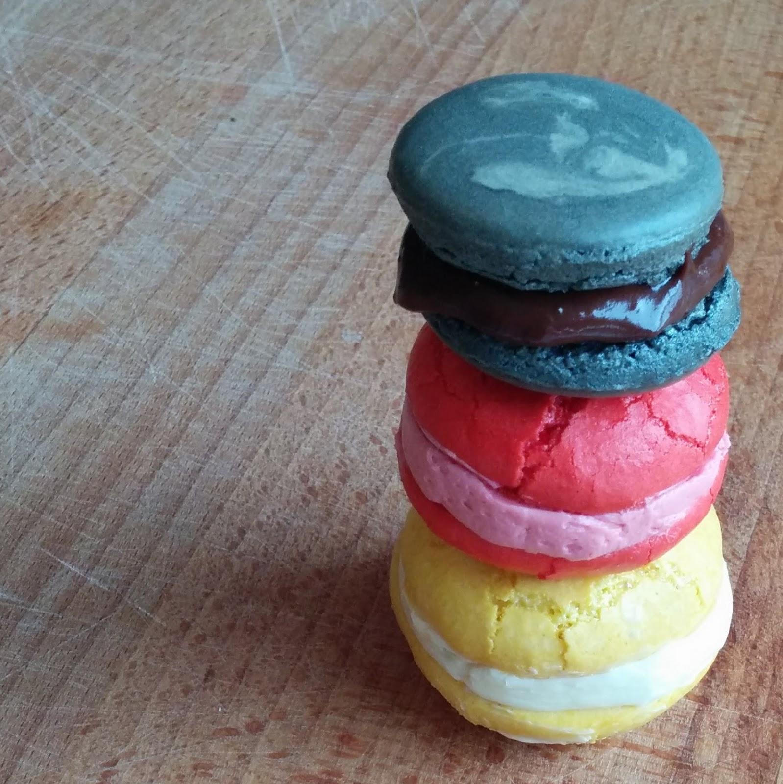 Macarons in den Nationalfarben schwarz, rot, gold / gelb auf einem Brett