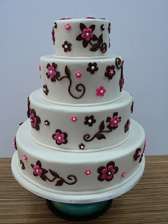 4 tier white wedding cake with black and pink flowers