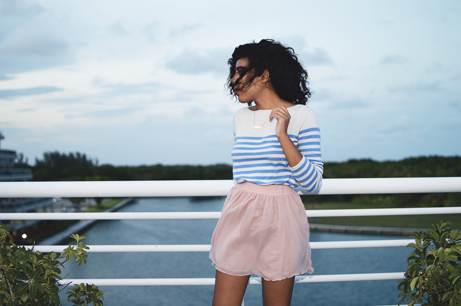 indie fashion blogger anais alexandre of down to stars in a light blue striped sweater and pink skirt with brown leather loafers at the marina