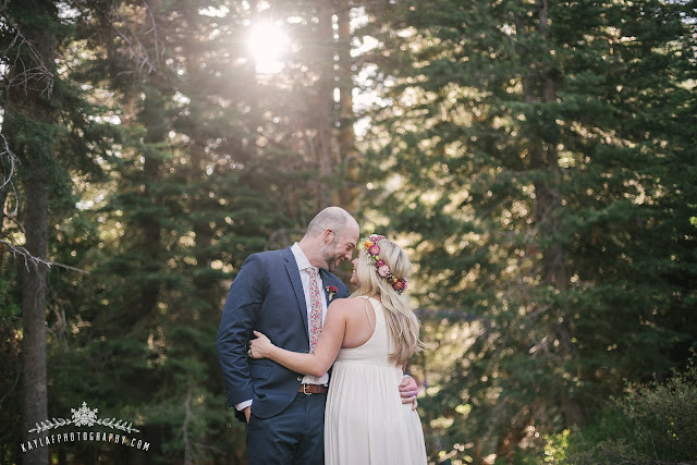 Private property wedding by the river in Squaw Valley, Lake Tahoe. Bride and Groom Photo - Bride wearing a long white flowy, jersey dress and flower crown. Groom wearing a navy suit; couple is surrounded by trees with the golden sun peaking through the trees.