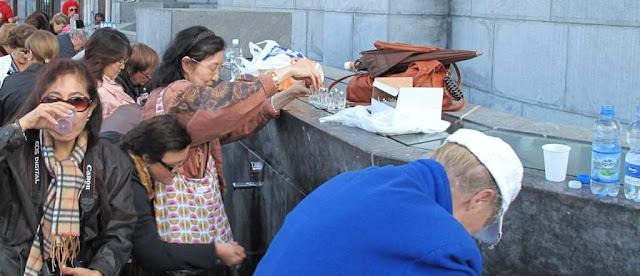Fiéis colhem água ao pé do Santuário de Lourdes