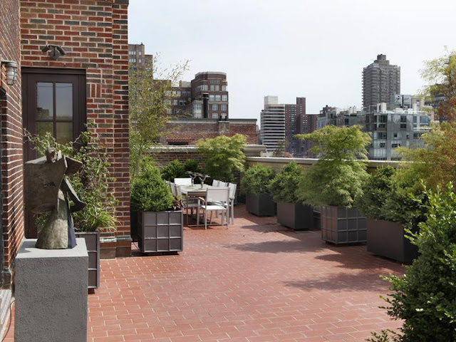 Outdoor terrace with brick floor, potted plants and a view of New York City