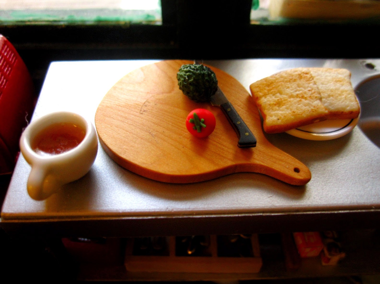 Modern dolls' house miniature stainless steel bench with a chopping board with a knife, an avocado and a tomato on it. Next to it is a plate of toast and a mug of tea.