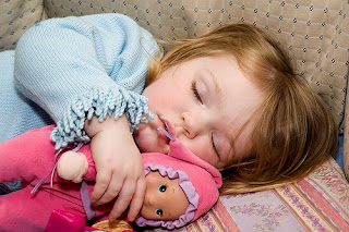 Little girl sleeping with her doll.
