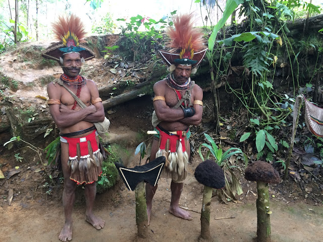 Huli tribesmen wear ceremonial wigs, with regular wigs on the two posts on the right