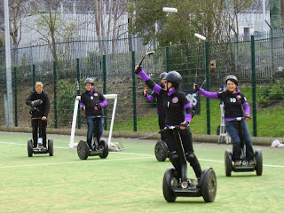 Four players in purple and black strip riding Segways, followed by sound recordist also on Segway