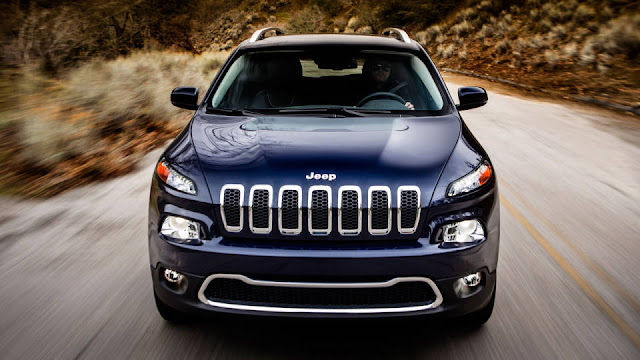Head on shot of the 2014 Jeep Cherokee driving on a two-lane road