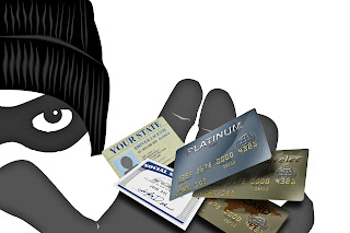 Masked thief holding various credit cards and identification items.