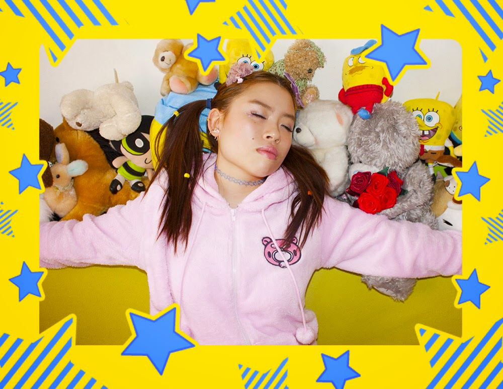Girl posing with pink gloomy bear hoodie and assorted soft toys