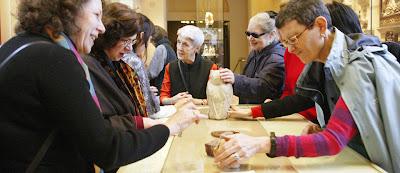 Conjunto de personas apreciando a través del tacto los objetos expuestos en el Victoria and Albert Museum.