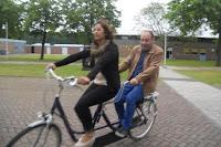 Fotografia de mais dois funcionários a pedalar no tandem