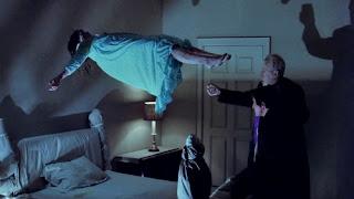 Fotograma que muestra a Regan levitando junto al padre Merrin