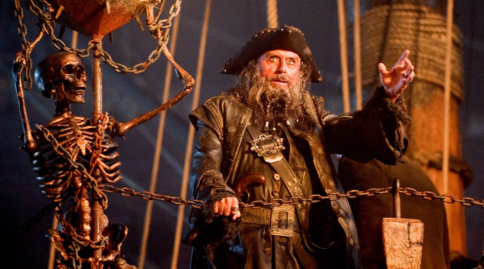 The fierce-looking Blackbeard stands next to a weathered skeleton.
