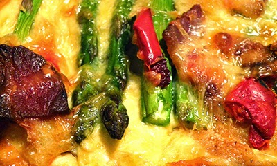 Strata Closeup Showing Bacon, Asparagus, Red Peppers and lots of Cheese