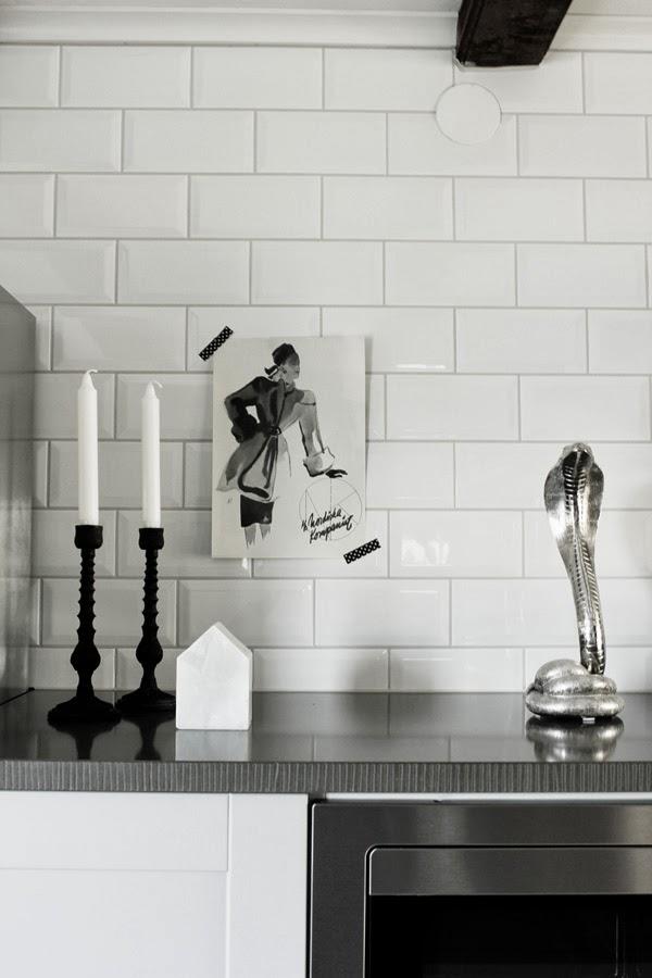 nk-annons, svart och vit bild på väggen, små kakelplattor, kakel 10X15 cm, vitt kakel i köket, industrikök, industrial kitchen, kobra i silver, silverdetalj, svarta ljusstakar, hus av marmor, washitejp med kors,svartvit tejp, stenskiva ovanför ugnen, olika nivåer i köket, inredning, interior,