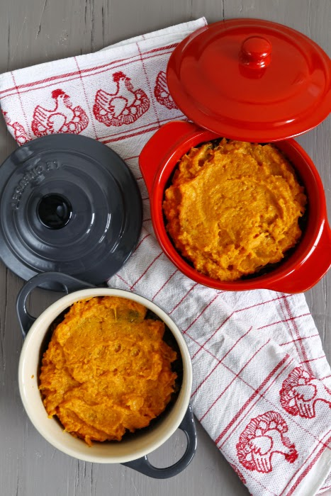 Two individual casserole dishes layed on a tea towel, filled with a vegetarian shepherd's pie