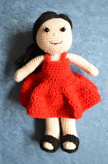 Kwokkie Doll is standing up, wearing a red sleeveless sundress and black sandals against a blue background.