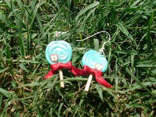 Boucles d'oreille en forme de sucettes bleu-vertes en pâte Fimo, ornées d'un ruban rouge et d'une petite tranche de pomme, déposées dans l'herbe