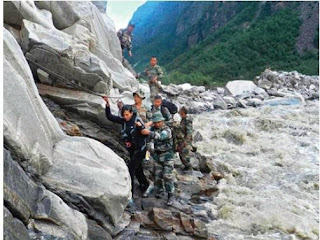 Army troops assist a stranded civilian to safety beside a raging river near the Pindari Glacier area of Uttarakhand