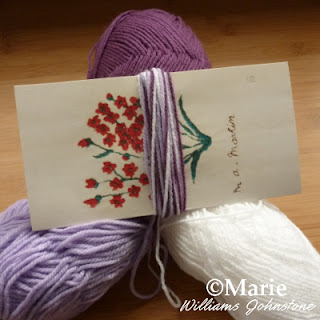 Purple, lilac and white yarn with yarn wrapped around a card