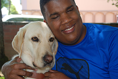 Jermey hugs his guide dog Spice - a Yellow Labrador Retriever
