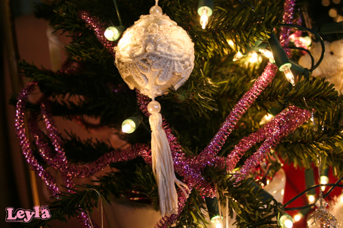 roze slingers en een witte kanten kerstbal met franjes